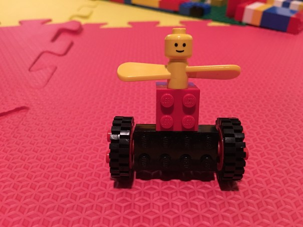 A Lego minifigure's head is attached to the shaft of a Basic propeller, forming arms, which is in turn mounted on Basic wheels