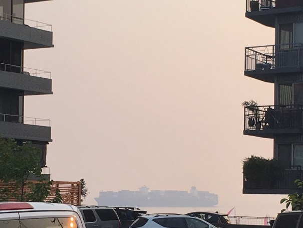 A huge container ship is barely visible through red-blue haze out in Elliott Bay, between two apartment buildings in Lower Queen Anne.