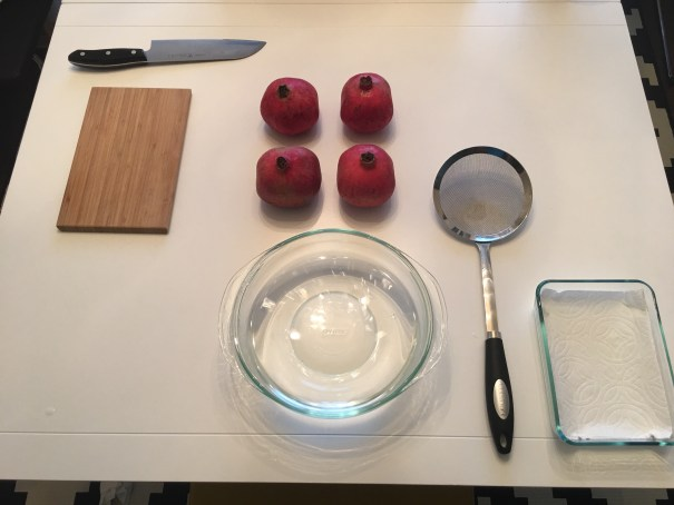 A white kitchen table is laid out with a large knife, a brown cutting board, four pomegranates, a glass bowl full of water, a strainer, and another glass bowl with paper towel lining.