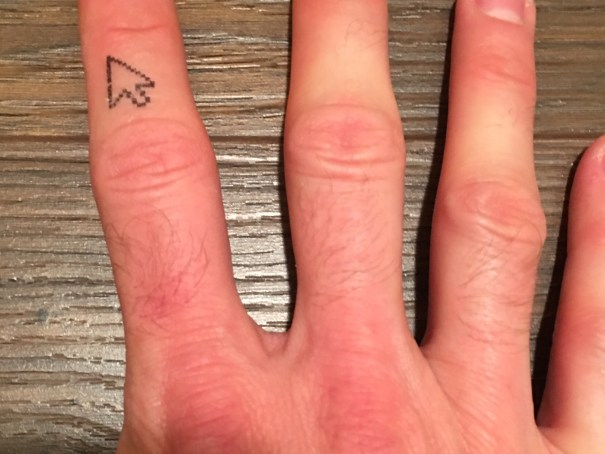 Four fingers of my right hand rest on a dark brown laminate floor. On the second knuckle of the index finger is a black outline of a Susan Kare style cursor.