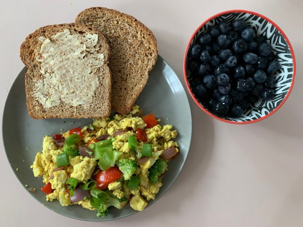Two slices of toast and yellow tofu scrambled with veggies sit on a grey plate with a bowl of blueberries nearby