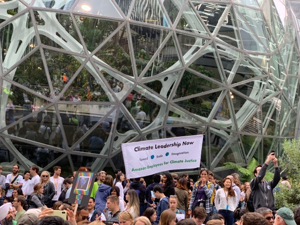 """A banner reading """"Climate Leadership Now"""" is carried between the crowd and The Spheres"""