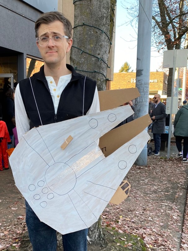 Nick is dressed as Han Solo (black vest white shirt) with a cardboard Millennium Falcon