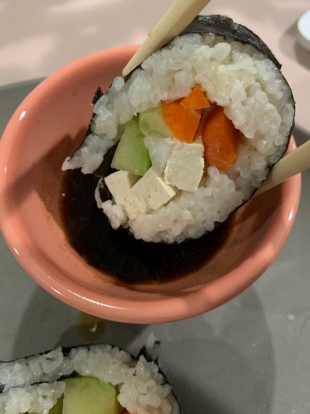 Closeup dipping a piece in wasabi tamari