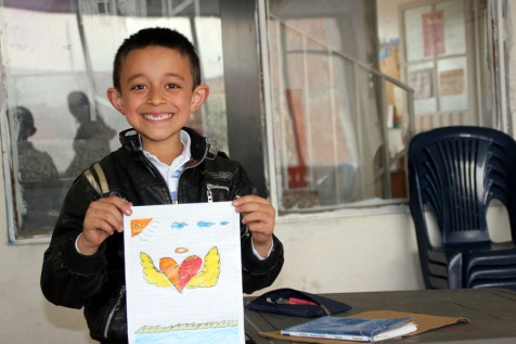 Jhonny holds up the drawing he made for his sponsor, Leiandro.