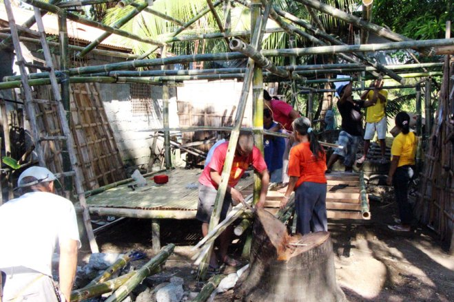 ERPAT fathers and other community members come together to rebuild sponsored elder Antonio's home.