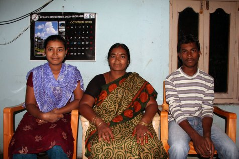 Savithri sits with her oldest daughter, Pravallika (left) and her son, Rajesh (right), who is sponsored.