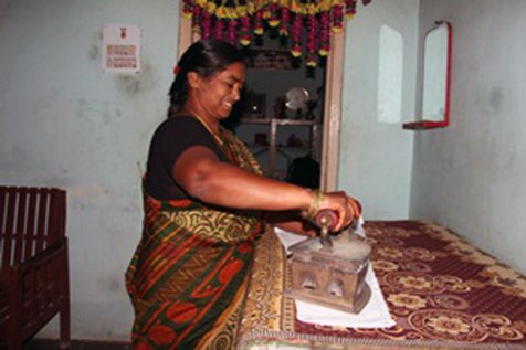 """Savithri uses a microloan from her Unbound mothers group to purchase this charcoal-fired """"iron box,"""" which helps her with her ironing."""