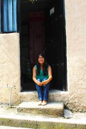 Jéssica sits in the doorway of her home in Mexico.