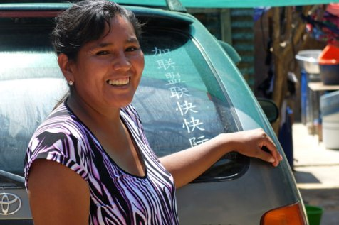 Luisa stands outside the taxi she drives in Bolivia.