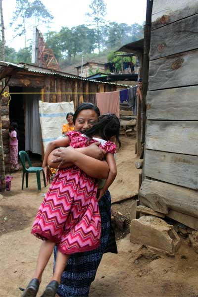 Sponsored child Aura from Guatemala is excited to see Unbound social worker Nidia.