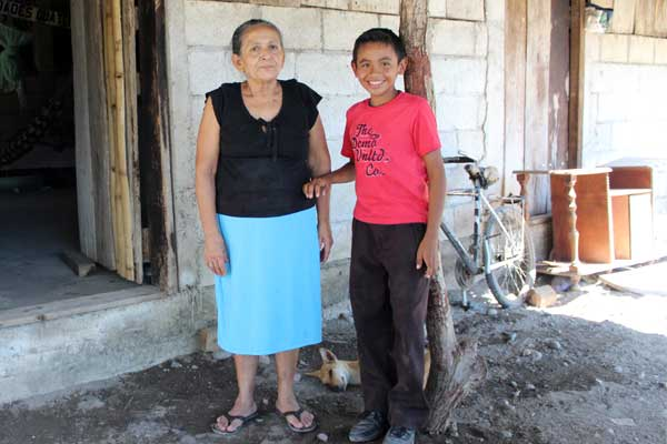 Bryan with his grandmother Lucia outside their home in Guatemala.