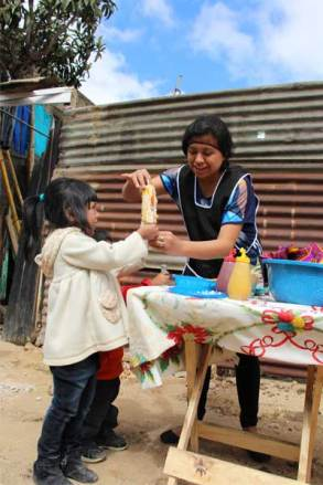 Maria delivers a freshly prepared elote loco to a young customer.