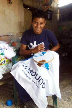 Fredy, 14, helps his mother with her embroidery business when not in school or studying.