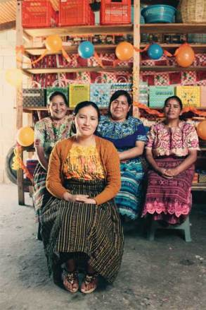 Members of a mothers group in Guatemala sit in front of baskets they produce to generate income. Pictured are Ana (foreground) and (in back, from left) Maria, Dora and Maria Eva.