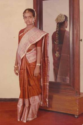 Pritha, at the age of 13, dressed for her coming-of-age ceremony. According to Pritha, this photo was taken in a professional photographer's studio, in front of a mirror so that the intricate braid work could be seen in the reflection.
