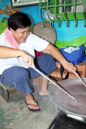 Aida stirs boiling rice, water and food coloring to turn the rice purple.