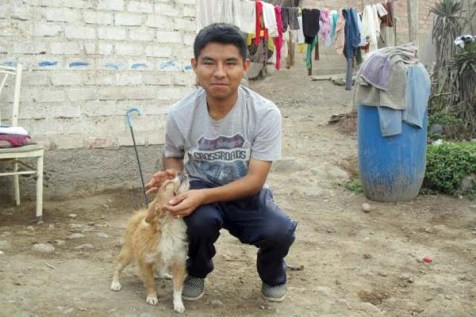 A young man in Peru kneels while petting a dog.