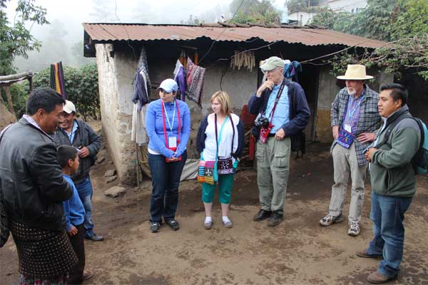 Awareness trip participants visit the home of a sponsored member in Guatemala along with local staff members.