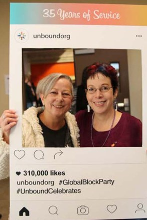 Two women hold up a giant Instagram frame and smile.
