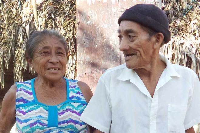 Eustaquia stands arm in arm with her husband, Felipe, outside their home. After his accident, she became the family's main provider.