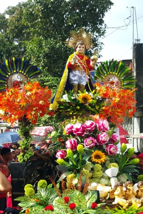 A statue of the child Jesus amidst flowers.