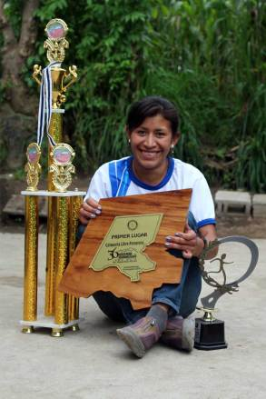 An image of Blanca with some of the trophies she has won at running competitions.