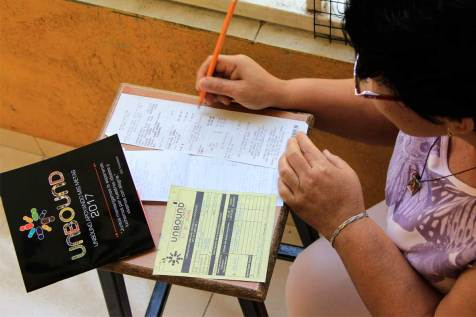 An image of a woman filling out a workbook.