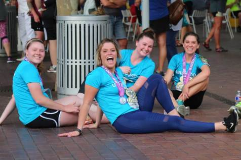 An image of four women sitting on the ground after running a 5K.