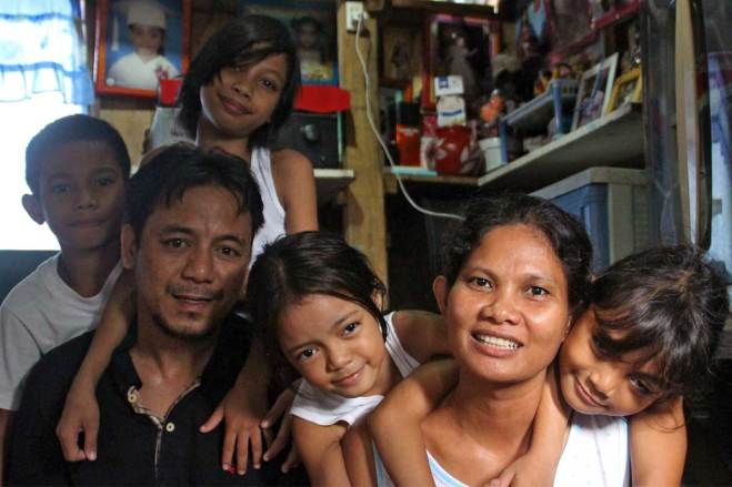 Sponsored child An-An (left, behind her father) shares a moment with her family in their small home. The others are, from left, Aaron, Ryan (father), Aria, Ely (mother) and Arianne.