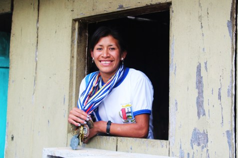 Blanca, the mother of a sponsored child in Guatemala, proudly wears medals she has won as a runner.