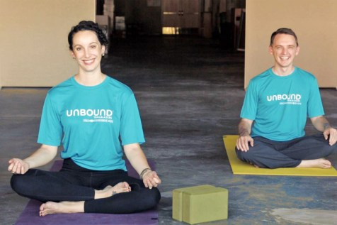 Maureen Lunn and Andrew Kling, Unbound's director of community outreach and media relations, wear Trailblazer t-shirts while doing yoga.