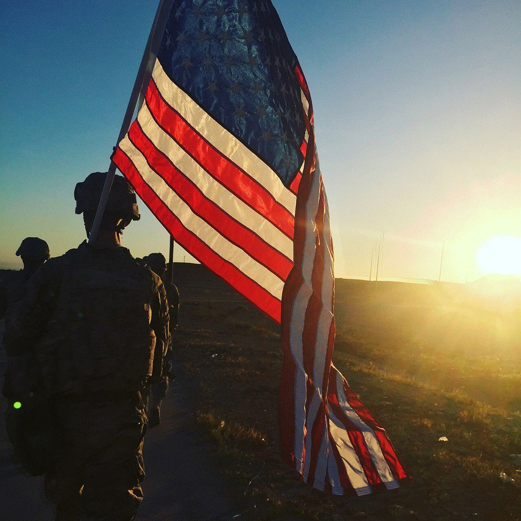 U.S. Army Sgt. Michael Swanker, assigned to the 1194th Engineer Company, 682nd Engineer Battalion, carries the American Flag during the 25K Danish Contingency, or DANCON, ruck march at Al Asad Air Base, Iraq.