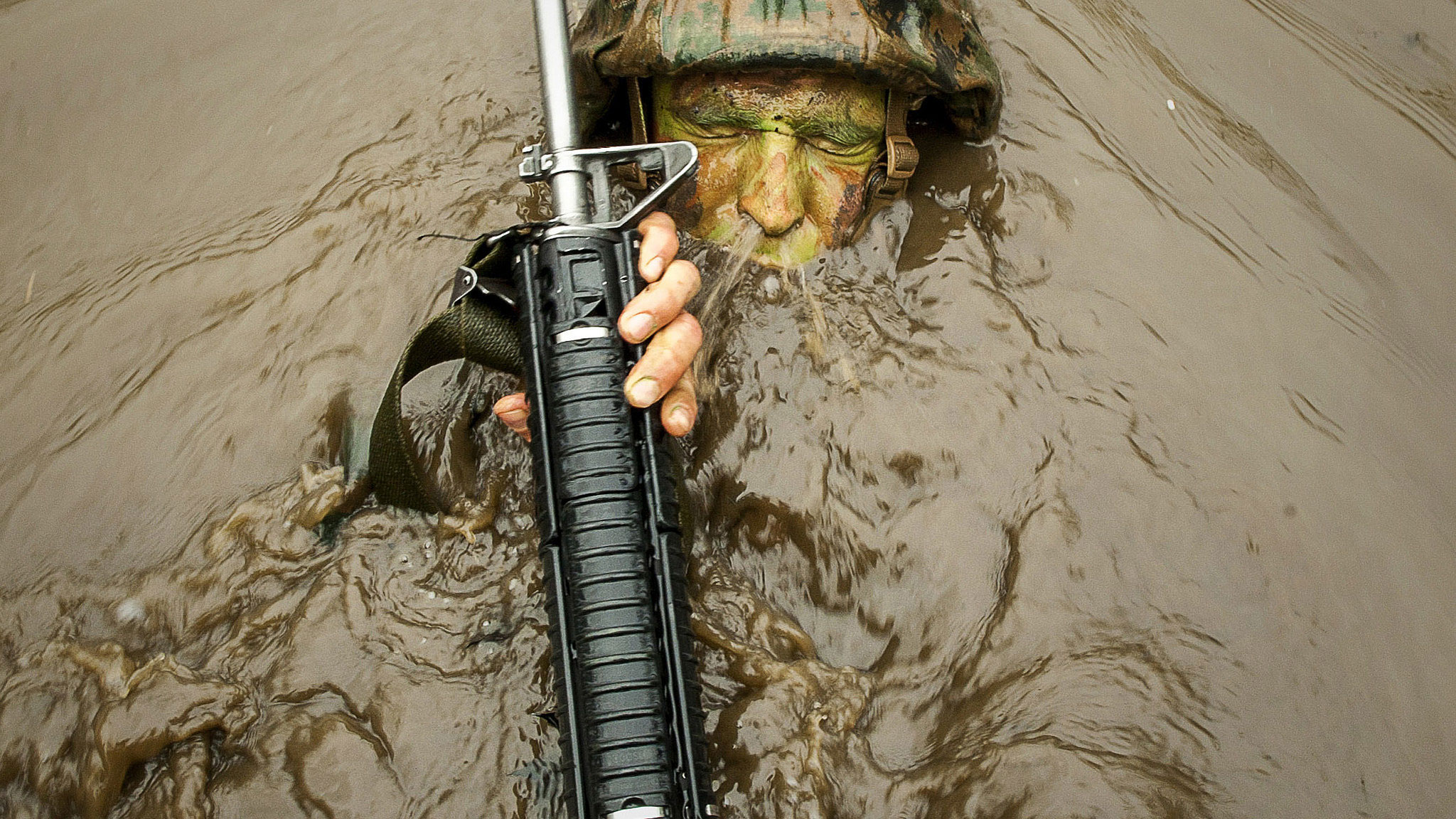 "A candidate assigned to Delta Company, Officer Candidates Class-221, breaks the surface of the murky water of 'The Quigley' at Brown Field, Marine Corps Base Quantico, Virginia. The mission of Officer Candidates School (OCS) is to ""educate and train officer candidates in Marine Corps knowledge and skills within a controlled, challenging, and chaotic environment in order to evaluate and screen individuals for the leadership, moral, mental, and physical qualities required for commissioning as a Marine Corps officer."""