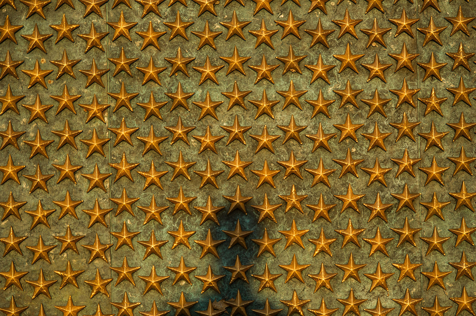 A shadow appears on the wall of stars at the National World War II Memorial in Washington D.C. The World War II Memorial honors the 16 million who served in the armed forces of the U.S., the more than 400,000 who died, and all who supported the war effort from home.