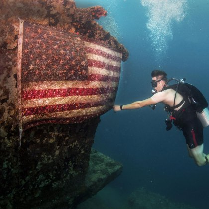 A U.S. Navy sailor fixes an American flag on the American Tanker, a sunken concrete barge used to transport fuel during World War II, in Apra Harbor, Guam, June 21, 2017.
