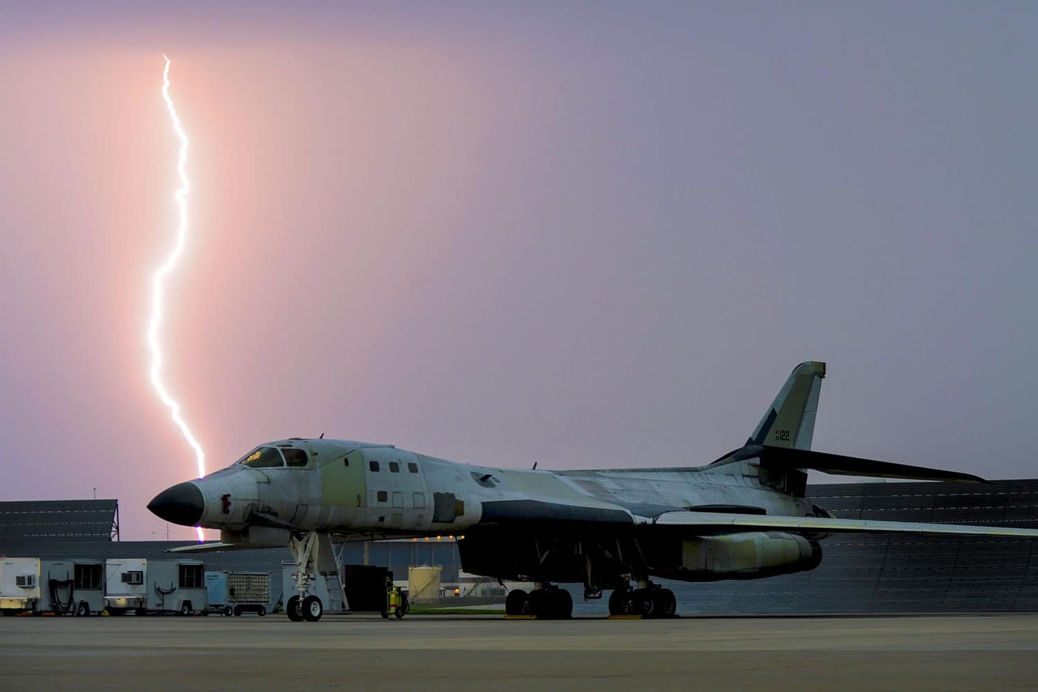 Lightning strikes behind a B-1B Lancer parked on the flight line as a major storm approaches Tinker Air Force Base, Okla. May 18, 2017. The B-1B is at Tinker AFB undergoing depot level maintenance and has been stripped of the majority of its paint.