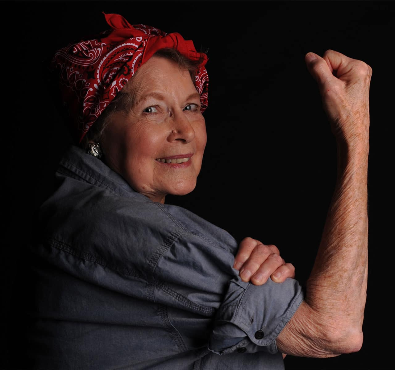 """Mary Ann Morden flexes her muscle in honor of """"Rosie the Riveter,"""" an iconic 1942 image of working women during World War II at Little Rock Air Force Base, Ark. After being a school teacher for 30 years, Mary Ann now volunteers assisting military retirees from across the state of Arkansas."""