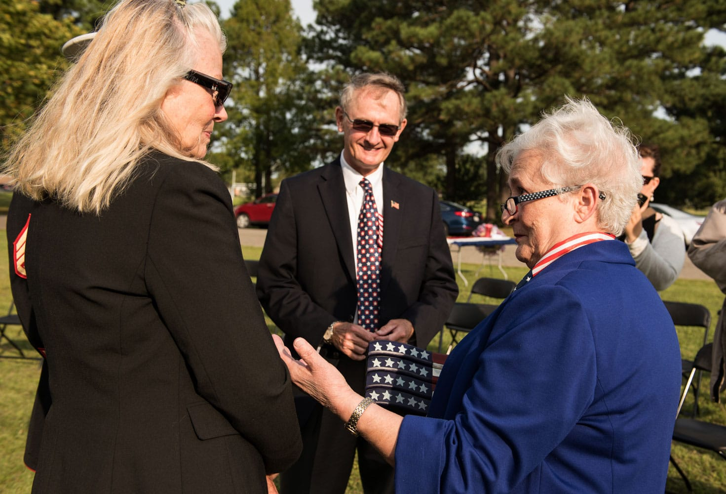 """The Honorable Angela Lee Leary, right, presents Claudia Johnson, Gold Star mother, a crafted flag during """"The Reading of The Names"""" at Gosnolds Hope Park, Hampton, Va., Sept. 11, 2017. Johnson's son United States Marine Corps 1st Lt. Michael Johnson, was killed Sept. 8, 2009 in the Kunar Province, Afghanistan."""