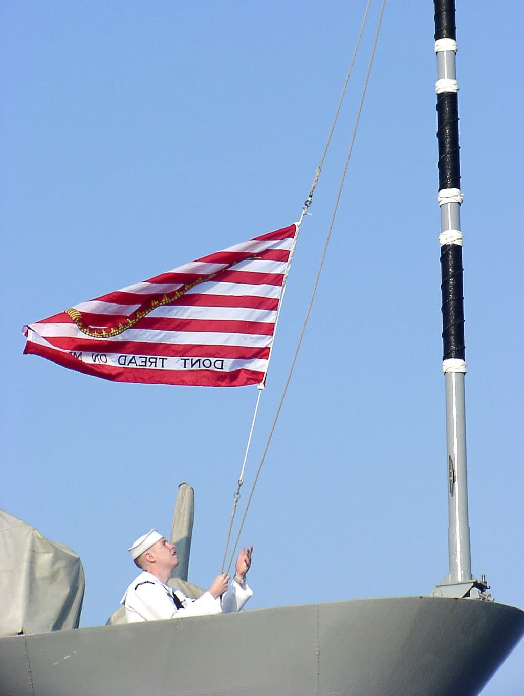 Operations Specialist 2nd Class Michael McKenna from Providence, R.I., raises the First Navy Jack flag for the first time at morning colors, on Sept. 11, 2002, aboard the guided missile cruiser USS Thomas S. Gates (CG 51).