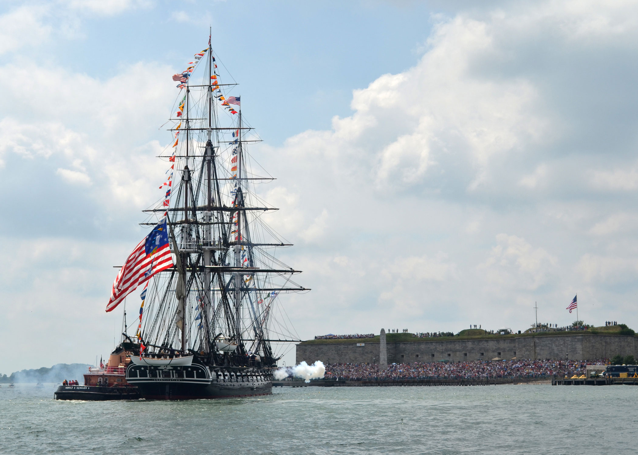 USS Constitution fires a 21-gun salute toward Fort Independence on Castle Island during the ship's July Fourth underway as part of an event for Boston Navy Week.