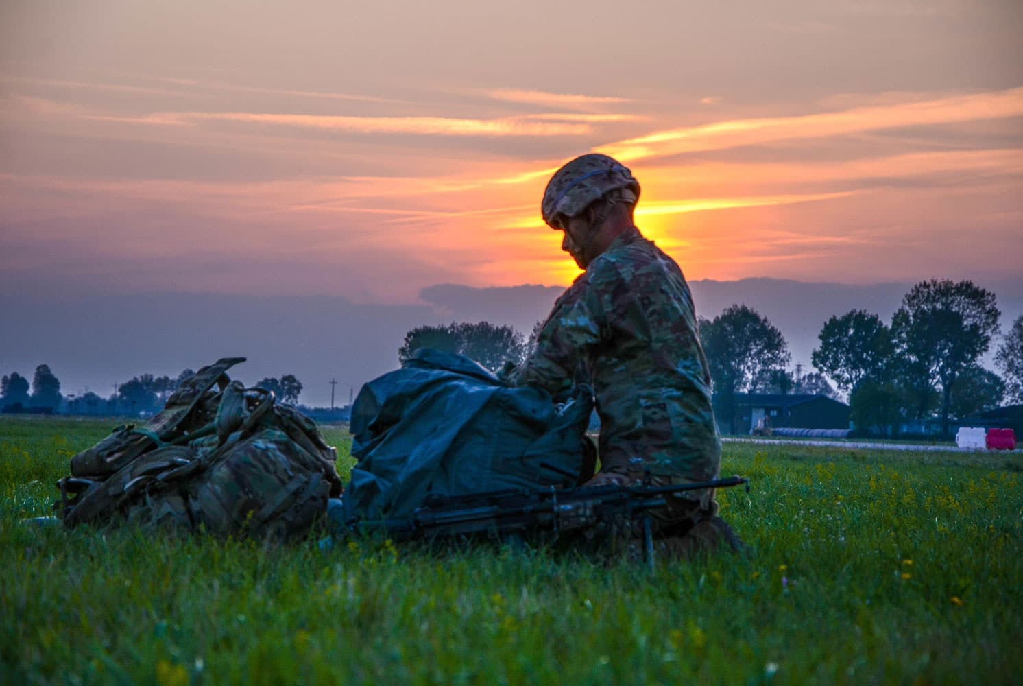 A paratrooper from the 173rd Airborne Brigade readies his gear after landing on the drop zone in Italy.