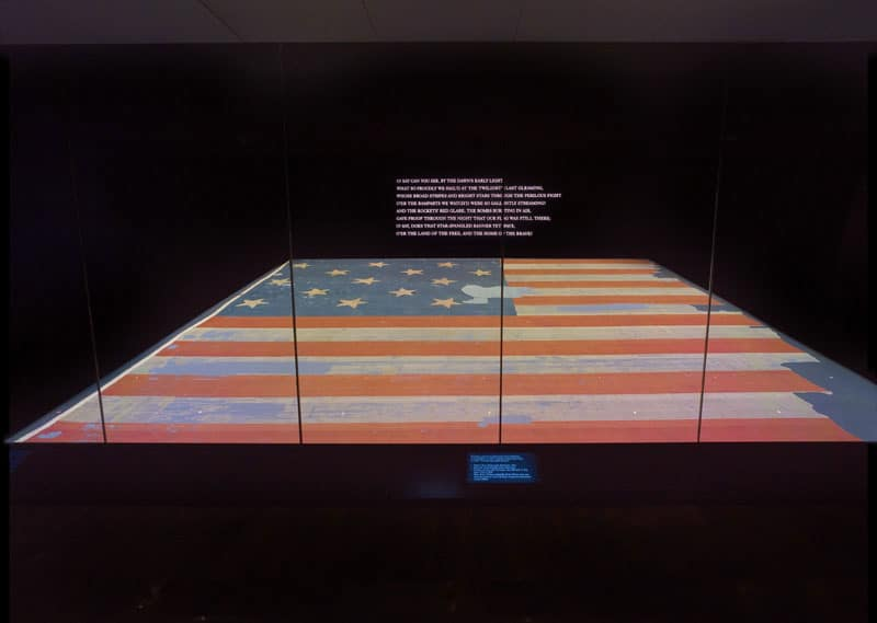 """Dawn's early light"" The first stanza of the national anthem is projected prominently on the wall above the Star Spangled Banner flag."