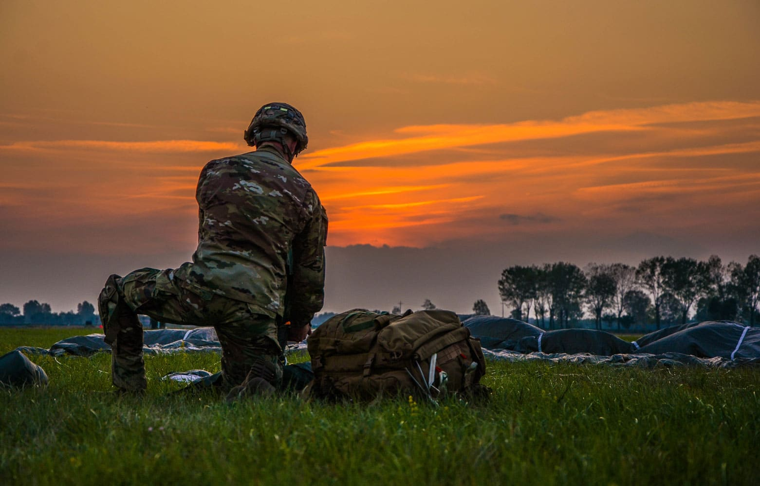 The setting sun highlights a paratrooper from the 173rd Airborne brigade as he collects his parachute after landing.
