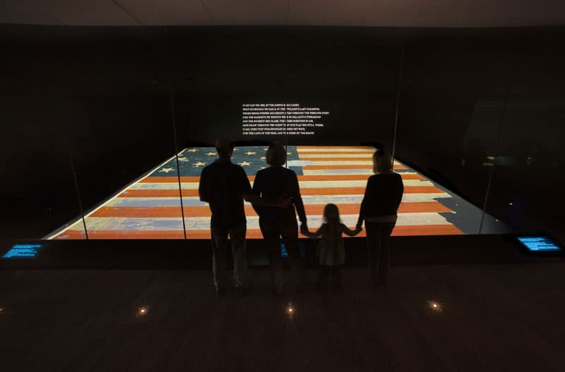 Visitors view the Star Spangled Banner flag.