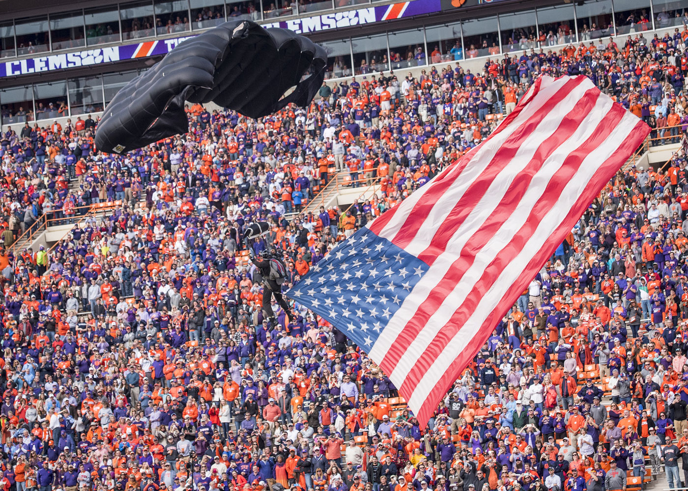 A paratrooper with the U.S. Army Special Forces Association Parachute Team from Fort Bragg parachutes into Clemson University's Memorial Stadium with the American flag before the Military Appreciation Game.