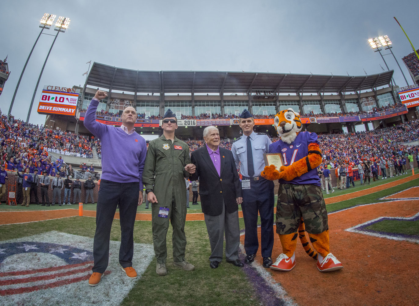 Retired U.S. Army Col. Ben Skardon, 100 (in dark jacket), is escorted onto the field of Memorial Stadium by Clemson president Jim Clements (left), the Clemson Tiger (right), and two Air Force ROTC cadets to be recognized as the Hero of the Game during the 2017 Military Appreciation Game.