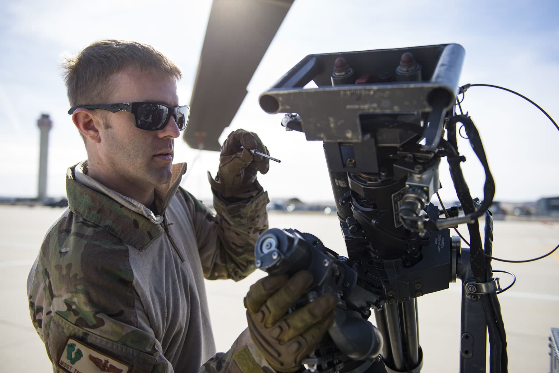 Master Sgt. Trevor Stevens, an evaluator flight engineer from the 943rd Rescue Group, inspects an M134 minigun attached to a HH-60G Pave Hawk helicopter, at Gowen Field, Idaho, during pre-deployment training for the 305th Rescue Squadron.
