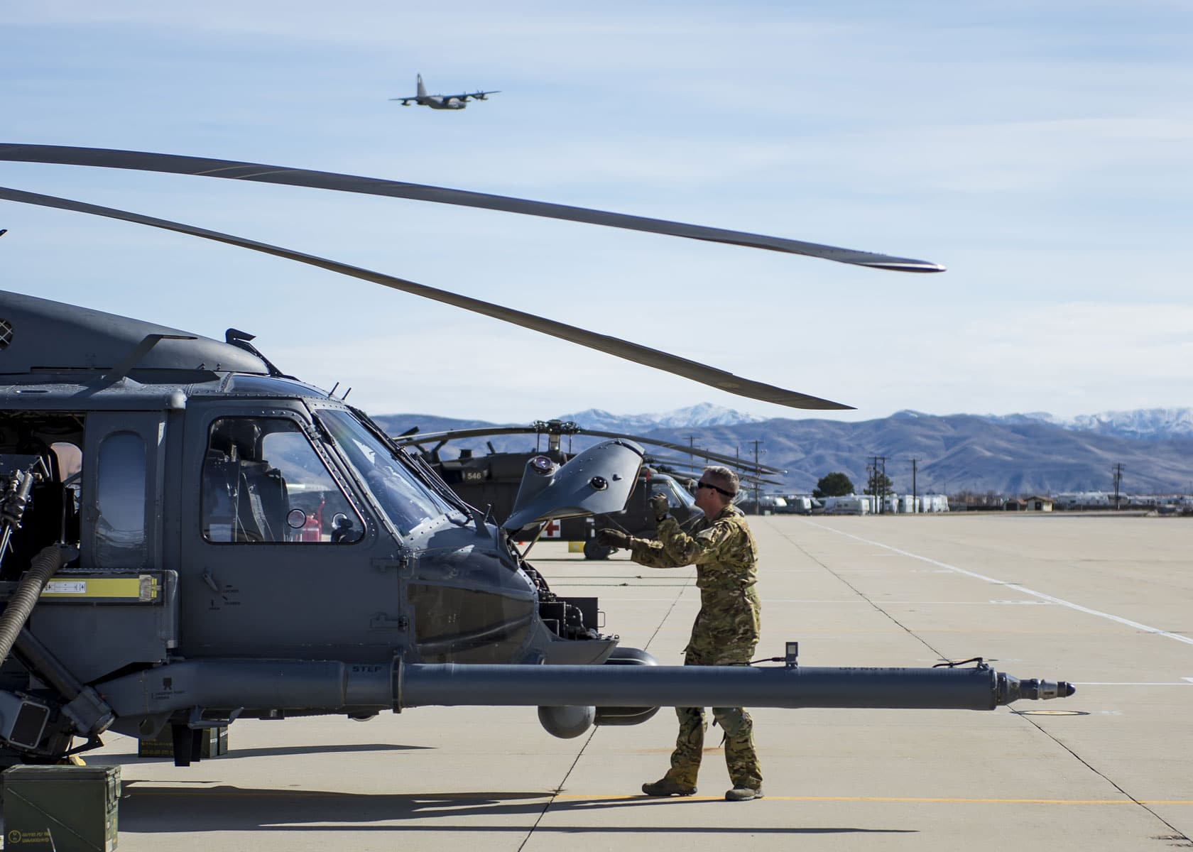 An Airman with the 943rd Rescue Group performs a pre-flight inspection on an HH-60G Pave Hawk helicopter as HC-130J Combat King II flies over head.