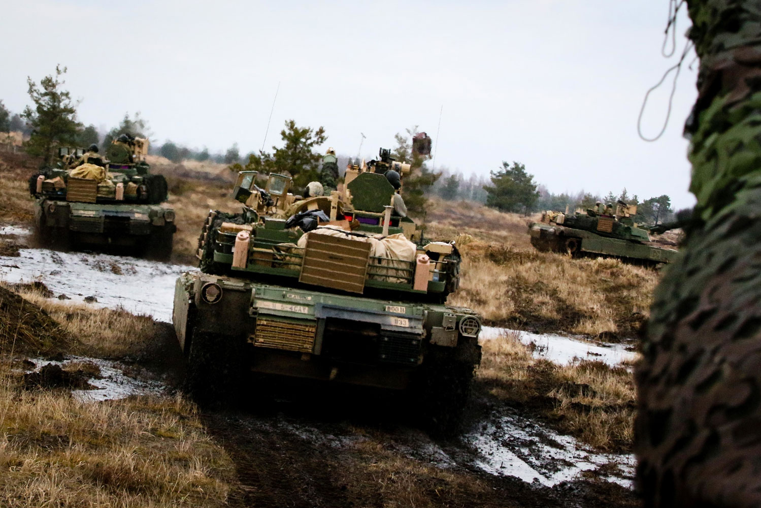 A group of M1A2 Abrams tanks move into firing positions during training.